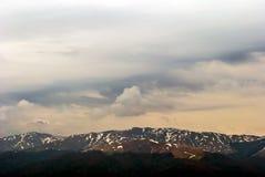Wiatr dorośleć chmury i śnieżną halnych szczytów markotną scenę Fotografia Stock
