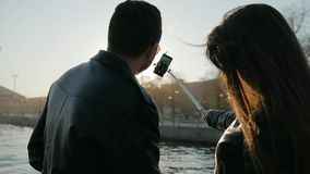 Wiatr rozwija włosy, tła światło, kochankowie robi fotografii na smartphone, selfi szczęśliwa potomstwo para fotografia, zbiory wideo