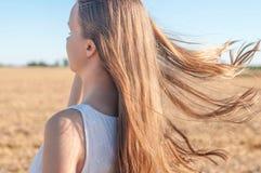 Wiatr trzepocze młodej dziewczyny długie włosy w polu Fotografia Stock