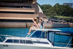 Wiatr zamiatał ładnej dziewczyny i młody człowiek siedział na dachu mknięcie prędkości łódź przed Sydney operą w Sydney, Australi zdjęcie stock