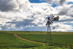 Wiatraczek obok drogi gruntowej w zielonym polu w Caledon, Zachodni przylądek, Południowa Afryka obrazy stock
