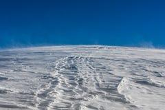 Wiatrowy szaleje i rusza się śnieg z niebieskiego nieba tłem, Passo Giau, Cortina d «Ampezzo, dolomity, Włochy zdjęcie stock