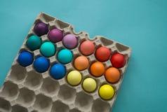 Wibrująca ręka farbujący kolorowi Wielkanocni jajka w kartonowym jajecznym pudełku przeglądać obraz royalty free