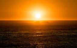 Wibrujący pomarańczowy zmierzch na oceanie z odbiciami na wody powierzchni i skałami w sylwetce obrazy royalty free