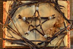 Wicca pentagram, moth - death symbol, and tree branches on open book with shabby pages in candle light, top view Stock Photo