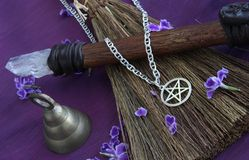 Wiccan Objects. Close up of wiccan objects - pentacle pendant, wood / crystal wand and straw besom Stock Photo