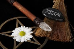 Wiccan Objects. Close up of wiccan objects - brass pentacle wand besom and flower on black background and wisdom stone Stock Photo