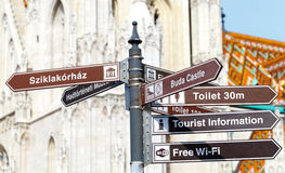 Wich one to take?. Picture of a cross sign column on an urban street with tourist information Royalty Free Stock Image