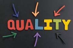 Wichtig und Bewusstsein des Qualitätskonzeptes, bunte Pfeile, die auf die Wort Qualität in der Mitte auf schwarzer Tafel zeigen lizenzfreie stockfotografie