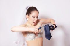 Wicked bride scissor a groom tie Royalty Free Stock Image