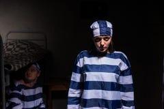 Wicked female prisoner wearing  prison uniform standing near bed Stock Photos