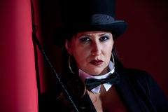 Wicked Female Ringmaster. Woman dressed like a circus ringmaster with riding crop Royalty Free Stock Image