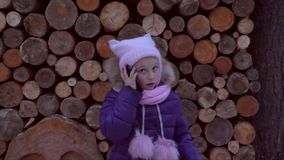Wicked girl talking by cell phone. Young caucasian girl swears by phone and steps from one side to other against. Background of a wooden texture. Outdoors stock video