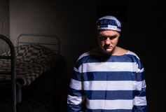 Wicked male prisoner wearing  prison uniform standing in a small Stock Image