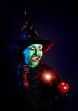 Wicked witch doing magic with her wand Stock Photo