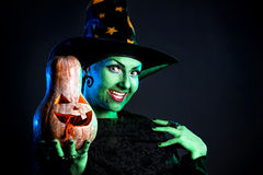 Wicked witch with pumpkin. Witch with green skin holding carved Halloween pumpkin at dark background Stock Images
