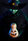Wicked witch with pumpkin stock image