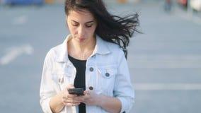 Wickeln Sie beeinflussendes braunes Haar des jungen kaukasischen Brunettemädchens wenn sie unter Verwendung ihres Smartphone Stea stock video footage