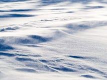 Wickeln Sie den Antriebschnee, der über Schneeoberfläche refief fliegt Stockfotos