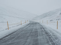 Wickeln Sie geblasener Schnee bedeckte Winterstraße mit Berg auf der Seite Lizenzfreies Stockbild