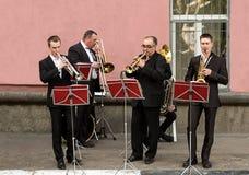 Wickeln Sie Straßenensemble-Saxophontrompete, eine Stadttagesfeier Vier Musiker in den klassischen schwarzen Anzügen spielen auf  lizenzfreie stockfotografie