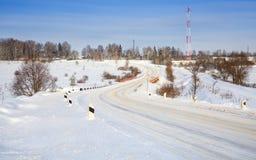 Wickelnde schneebedeckte Straße durch die Brücke Stockbilder