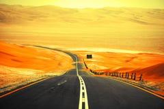 Wickelnde schwarze Asphaltstraße durch die Sanddünen von Liwa-Oase, Vereinigte Arabische Emirate Lizenzfreies Stockfoto