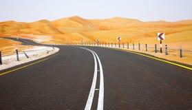 Wickelnde schwarze Asphaltstraße durch die Sanddünen von Liwa-Oase, Vereinigte Arabische Emirate Lizenzfreie Stockfotos
