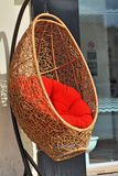 Wicker armchair with red cushions Stock Image