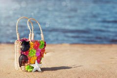 Wicker bag and sunglasses on the beach Stock Images