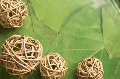 Wicker balls, green background. Wicker balls and water on a peaceful 'leafy' green background with copy space Royalty Free Stock Photo