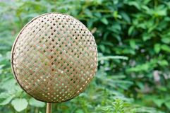 Wicker bamboo basket hanging on bamboo stick with copy space Stock Photo