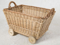 Wicker basket. Hand-made wicker box on wheels with two handles Royalty Free Stock Images