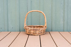 Wicker basket against green wall Stock Photography