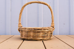 Wicker basket against lilac wall Royalty Free Stock Photos
