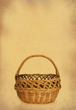 Wicker basket against stained retro paper stock image