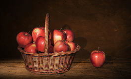 Wicker Basket with apples and one apple on table, dark painting background. Royalty Free Stock Images