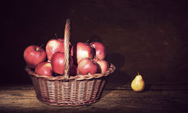 Wicker Basket with apples and one pears on table, dark painting background. Royalty Free Stock Image