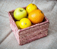 Wicker basket with apples, oranges and lemons, healthy food them Royalty Free Stock Images