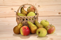Wicker basket with apples and pears on wooden background Stock Photos