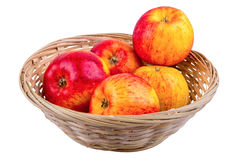 Wicker basket with apples on a white background. Wicker basket with apples isolated on a white background stock photo