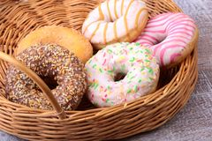 Wicker basket with assorted delicious homemade doughnuts in the glaze, colorful sprinkles and nuts . Wicker basket with assorted delicious homemade doughnuts in stock images