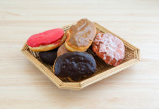 Wicker basket with assorted donuts on wood table top Stock Images