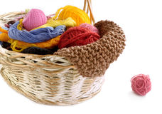 Wicker basket with balls of yarn and knitting needles. Threads of different types are in a wicker basket for needlework Stock Image
