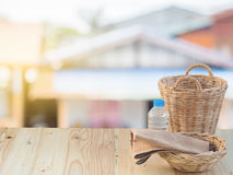 Wicker basket, bottle and fabric on wooden terrace pine. Royalty Free Stock Images