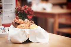 Wicker basket with bread. Bread and buns inside basket. Fresh bakery products on table. Tastes best when warm. Wicker basket with bread. Bread and buns inside Royalty Free Stock Photography