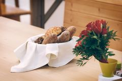 Wicker basket with bread. Bread and buns inside basket. Fresh bakery products on table. Tastes best when warm. Wicker basket with bread. Bread and buns inside Royalty Free Stock Image