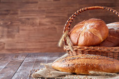 Wicker basket with bread. Bread and buns inside basket. On the wooden table. Stock Photography