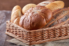 Wicker basket with bread. Bread and buns inside basket. On the wooden table. Wicker basket with bread. Bread and buns inside basket. Fresh bakery products on royalty free stock images