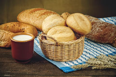 Wicker basket with bread products and milk cup on the tablecloth Royalty Free Stock Images